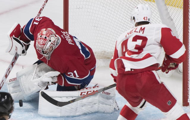 Montreal Canadiens goaltender Carey Price, left, makes a save against Detroit Red Wings' Darren Helm during third-period NHL hockey game action in Montreal, Thursday, Oct. 10, 2019. (Graham Hughes/The Canadian Press via AP)
