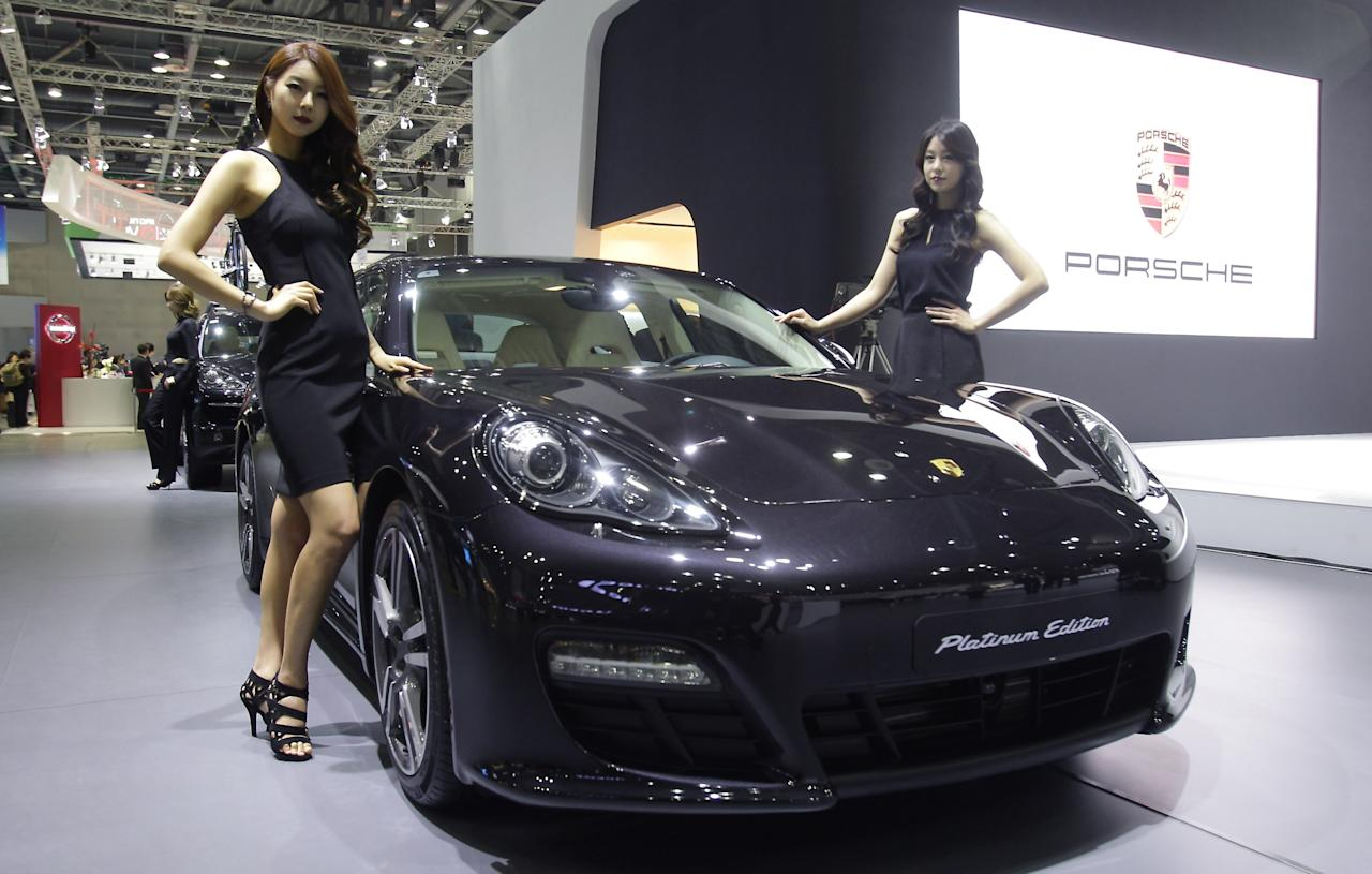 GOYANG, SOUTH KOREA - MARCH 28:  Models pose next to a Porsche Panamera Platium Edition at the Seoul Motor Show 2013 on March 28, 2013 in Goyang, South Korea. The Seoul Motor Show 2013 will be held in March 29-April 7, featuring state-of-the-art technologies and concept cars from global automakers. The show is its ninth since the first one was held in 1995. About 384 companies from 14 countries, including auto parts manufacturers and tire makers, will set up booths to showcase trends in their respective industries, and to promote their latest products during the show.  (Photo by Chung Sung-Jun/Getty Images)