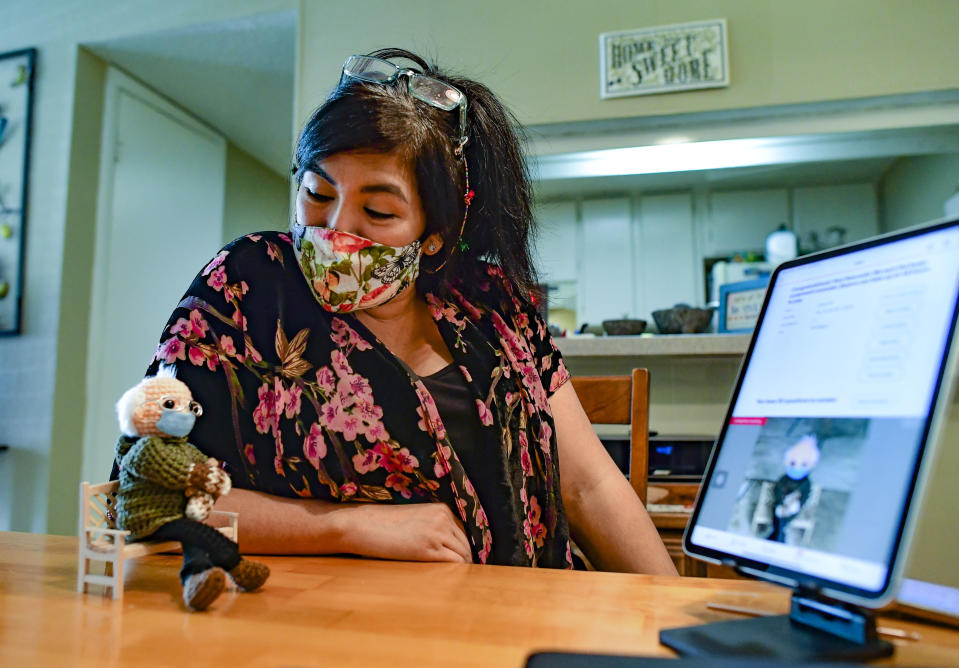 Tobey King speaks to her crochet Bernie Sanders doll as the bidding continues on eBay on Tuesday, Jan. 26, 2021 in Corpus Christi, Texas. The doll sold for $20,300, and all of the proceeds are being donated to Meals on Wheels. (Billy Calzada/The San Antonio Express-News via AP)