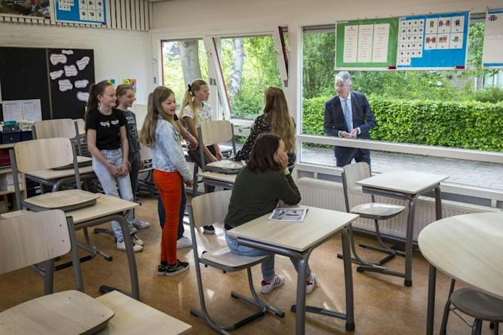Netherlands Primary and Secondary Education and Media Minister Arie Slob greets students through a window at a school in Zwolle (AFP Photo/Vincent JANNINK)