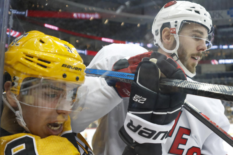 Pittsburgh Penguins' Evan Rodrigues (9) is checked by Carolina Hurricanes' Joel Edmundson (6) along the boards by during the second period of an NHL hockey game, Sunday, March 8, 2020, in Pittsburgh. The Hurricanes won 6-2. (AP Photo/Keith Srakocic)