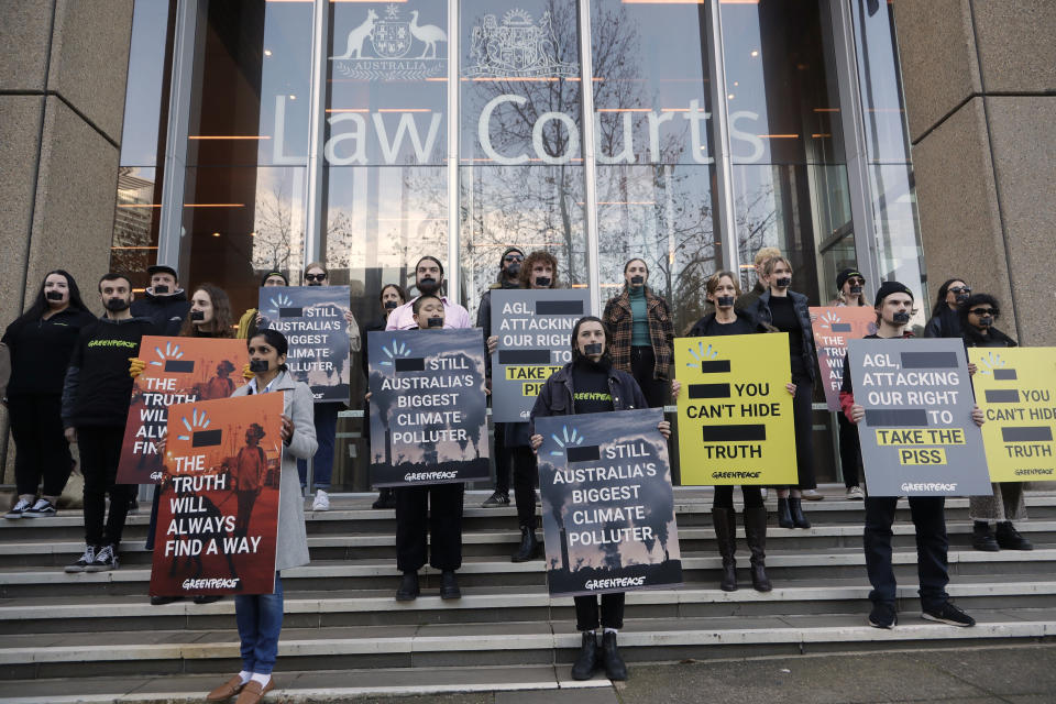 """Greenpeace supporters demonstrate outside the Federal Court in Sydney, Wednesday, June 2, 2021. Australia's largest electricity generator AGL Energy is taking Greenpeace to court alleging breaches of copyright and trademark laws in the environmental charity's campaign that describes AGL as the nation's """"biggest climate polluter."""" (AP Photo/Rick Rycroft)"""