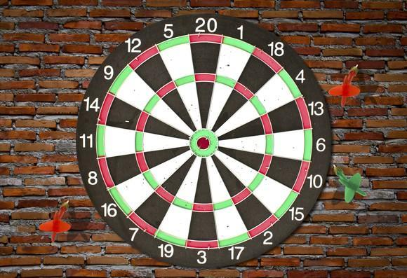 A dartboard with three darts that've completely missed the board.