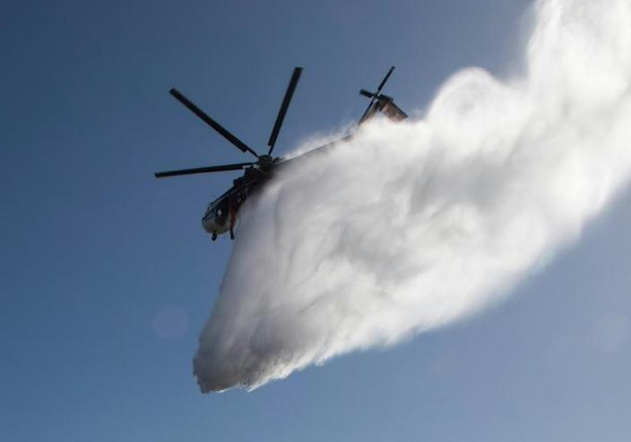 Water dropped by a helicopter lands on flames burning near the Reagan Library during the Easy Fire in Simi Valley, California on October 30, 2019 (AFP Photo/Mark RALSTON)