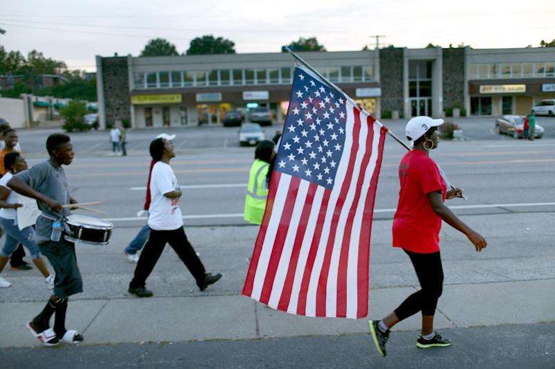 Demonstrators protesting the shooting death of Michael Brown march through the streets of Ferguson, Missouri, on August 22, 2014 (AFP Photo/Joe Raedle)