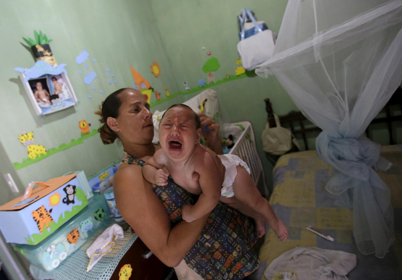 Josemary da Silva, 34, combs the hair of 5-month-old Gilberto, who was born with microcephaly, after giving him a bath at her house in Algodao de Jandaira, Brazil February 17, 2016. To match Special Report HEALTH-WHO/LEADER  REUTERS/Ricardo Moraes/File Photo