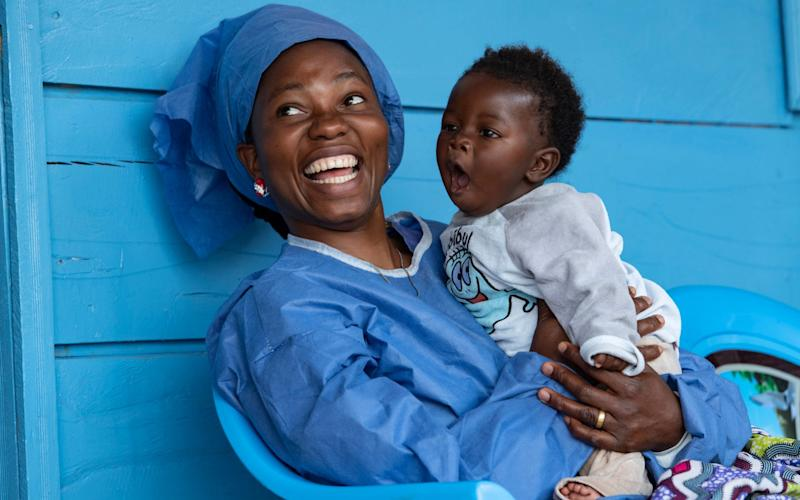 """Joniste Kahambu, whose three-year-old son died of Ebola during the current long-running outbreak, works as a """"lullaby singer"""", caring for children with the disease - Simon Townsley"""