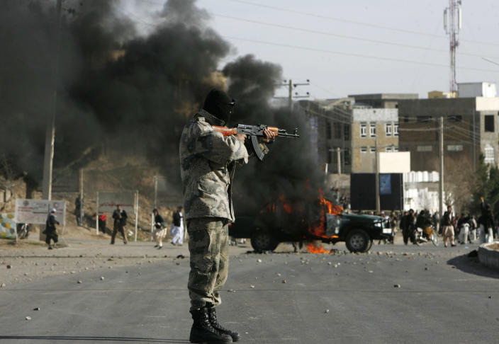 Afghan policeman aims at protesters by a burning police truck set alight during an anti-US demonstration over burning of Qurans at a US military base in Afghanistan, in Herat, Friday, Feb. 24, 2012. (AP Photo/Hoshang Hashimi)