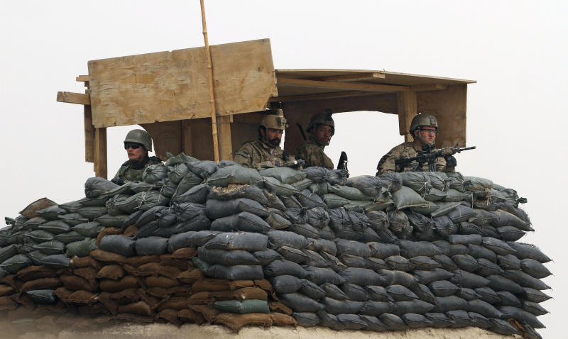 """U.S. Army and Afghan soldiers are seen in a guard tower at their base in Panjwai, Kandahar province south of Kabul, Afghanistan, Sunday, March 11, 2012. Afghan President Hamid Karzai says a U.S. service member has killed more than a dozen people in a shooting including nine children and three women. Karzai called the attack Sunday """"an assassination"""" and demanded an explanation from the United States. He says several people were also wounded in the attack on two villages near a U.S. base in the southern province of Kandahar. (AP Photo/Allauddin Khan)"""
