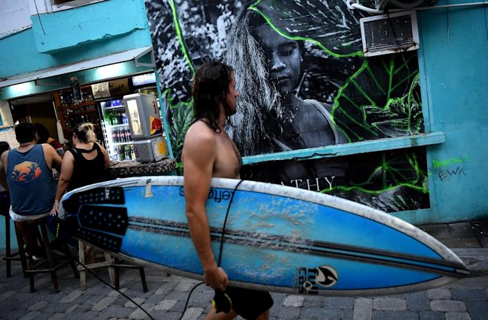 A surfer walks by a mural of Katherine Diaz.