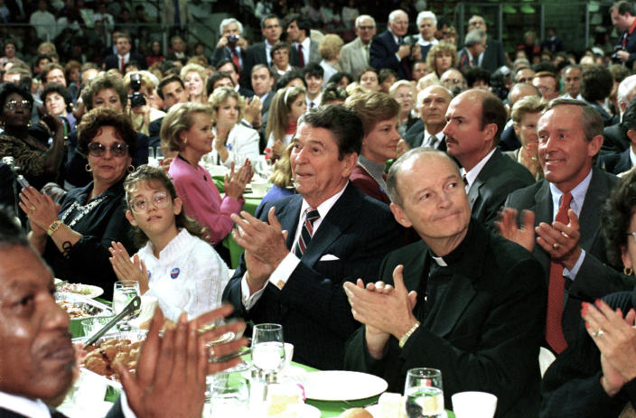 FILE - In this Oct. 12, 1988 file photo, President Ronald Reagan, center, and Newark Archbishop Theodore McCarrick, right, attend a Republican party campaign stop in West Orange, N.J. On Tuesday, Nov. 10, 2020, the Vatican is taking the extraordinary step of publishing its two-year investigation into the disgraced ex-Cardinal McCarrick, who was defrocked in 2019 after the Vatican determined that years of rumors that he was a sexual predator were true. (AP Photo/Barry Thumma)