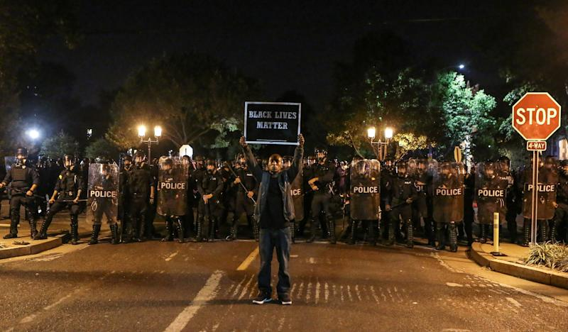 A Black Lives Matter protester stands in front of St. Louis Police Department officers equipped with riot gear on Sept. 15, 2017. (Lawrence Bryant / Reuters)