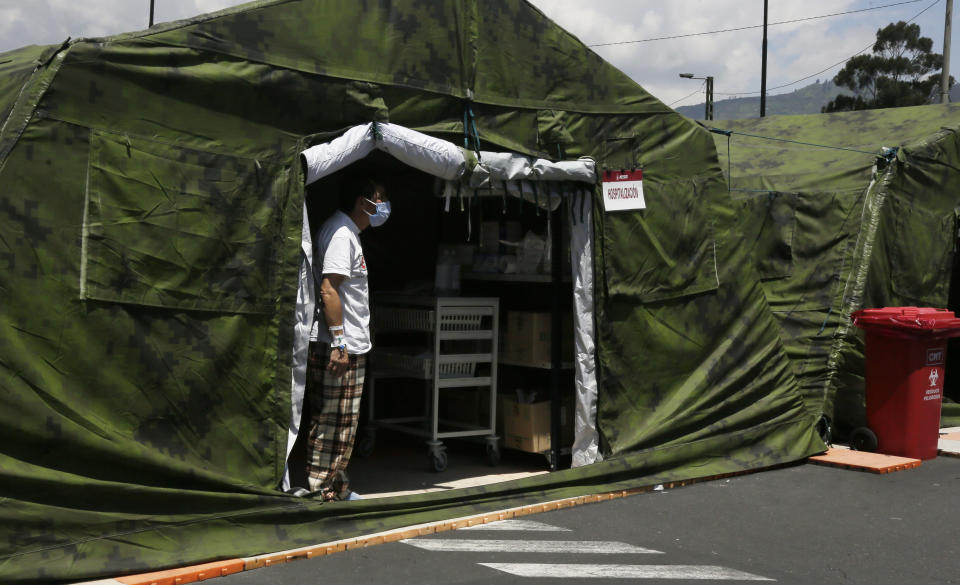 A COVID-19 patient looks for a relative to bring him personal items, from inside a tent set up outside the Social Security Hospital where patients are being treated in Quito, Ecuador, Thursday, April 22, 2021. The government decreed new lockdown rules on April 21 for the majority of Ecuador's provinces, limiting movement on weeknights and an all-day curfew on weekends to curb the spread of the new coronavirus which is overwhelming hospitals. (AP Photo/Dolores Ochoa)
