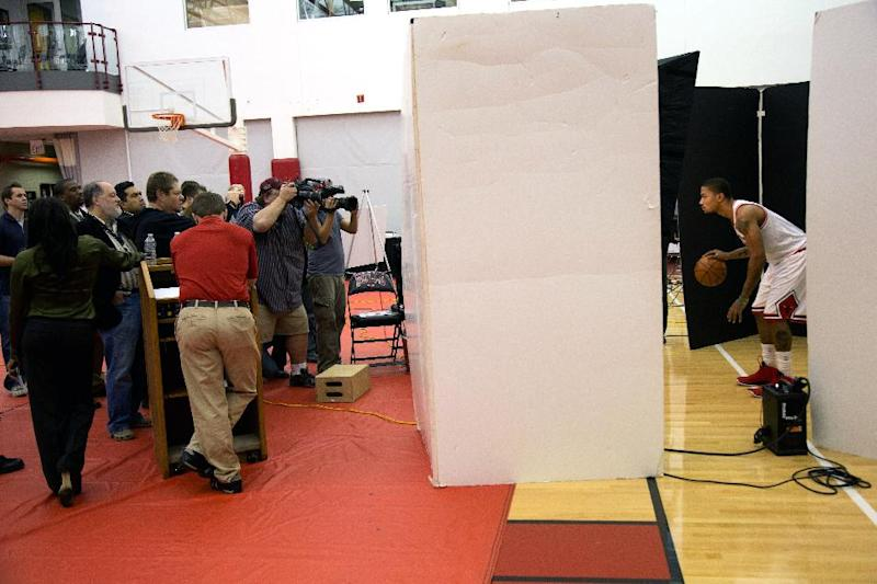 Photographers take pictures of Chicago Bulls' Derrick Rose, right, during the NBA basketball team's media day at the Bulls' practice facility, Monday, Oct. 1, 2012, in Deerfield, Ill. (AP Photo/Charles Cherney)