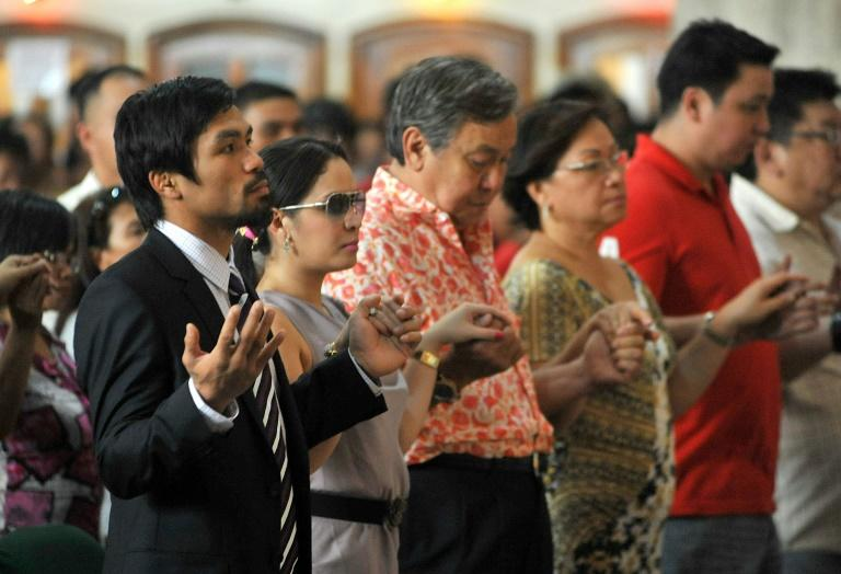 Philippine boxing hero Manny Pacquiao (L) holds his wife Jinkee's hand as they attend a mass at the Quiapo church in Manila, in 2010