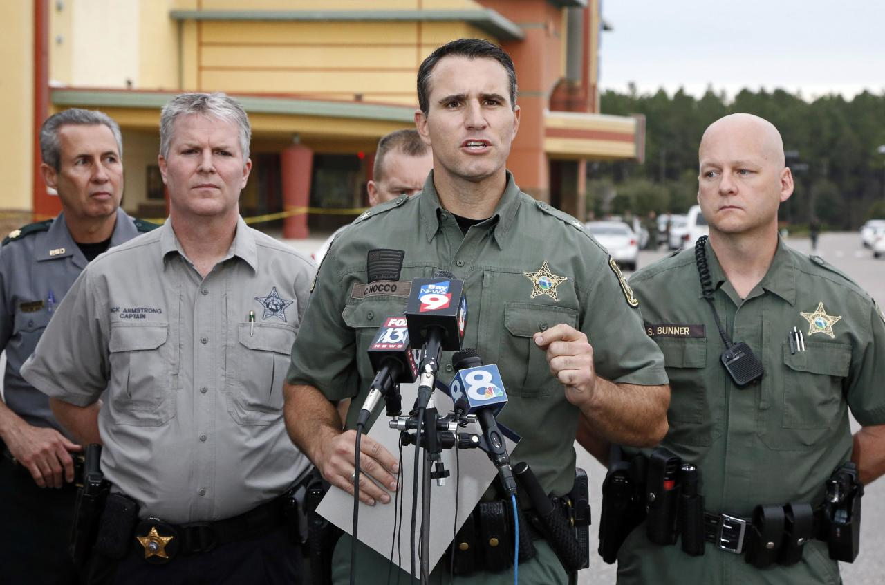 "Pasco County Sheriff Chris Nocco (C) speaks to the media as police tape surrounds the Cobb Grove 16 movie theater in Wesley Chapel, Florida, January 13, 2014. A moviegoer shot and killed one person and wounded another on Monday when an argument over text messaging in a Florida theater showing the hit new war film ""Lone Survivor"" erupted in gunfire, authorities said. REUTERS/Mike Carlson (UNITED STATES - Tags: CRIME LAW)"