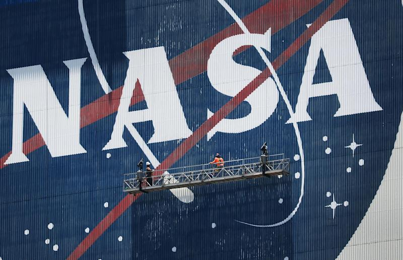 Workers freshen up the paint on the NASA logo on the Vehicle Assembly Building before the arrival of NASA astronauts Bob Behnken and Doug Hurley at the Kennedy Space Center on May 20, 2020 in Cape Canaveral, Florida: Joe Raedle/Getty Images