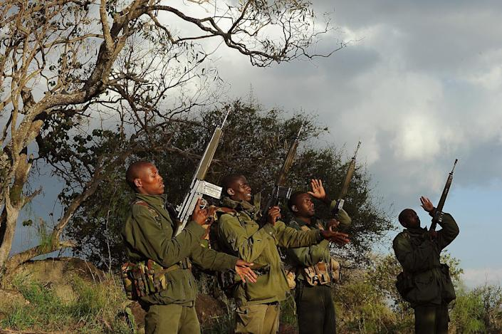 Members of an elite ranger team carry out an arms check before embarking on a night patrol at the Ol Jogi rhino sanctuary in Nairobi on August 7, 2014 (AFP Photo/Tony Karumba)