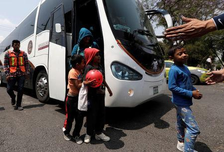 A Mexican police officer gestures as migrants from Honduras get off the bus, part of a caravan of Central American migrants moving through Mexico toward the U.S. border, in Puebla, Mexico April 6, 2018. REUTERS/Henry Romero