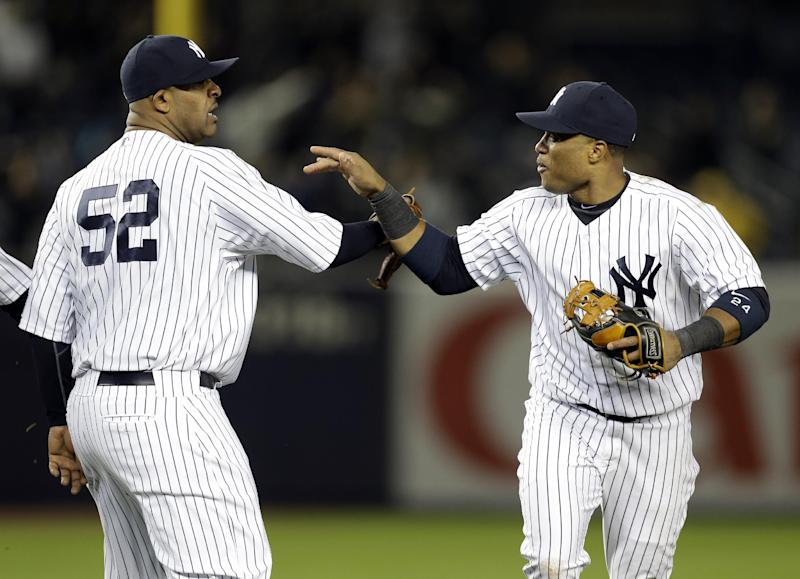 New York Yankees second baseman Robinson Cano, right, celebrates with starting pitcher CC Sabathia after the Yankees completed a triple play during the eight inning of a baseball game against the Baltimore Orioles at Yankee Stadium in New York, Friday, April 12, 2013. The Yankees won 5-2. (AP Photo/Julio Cortez)