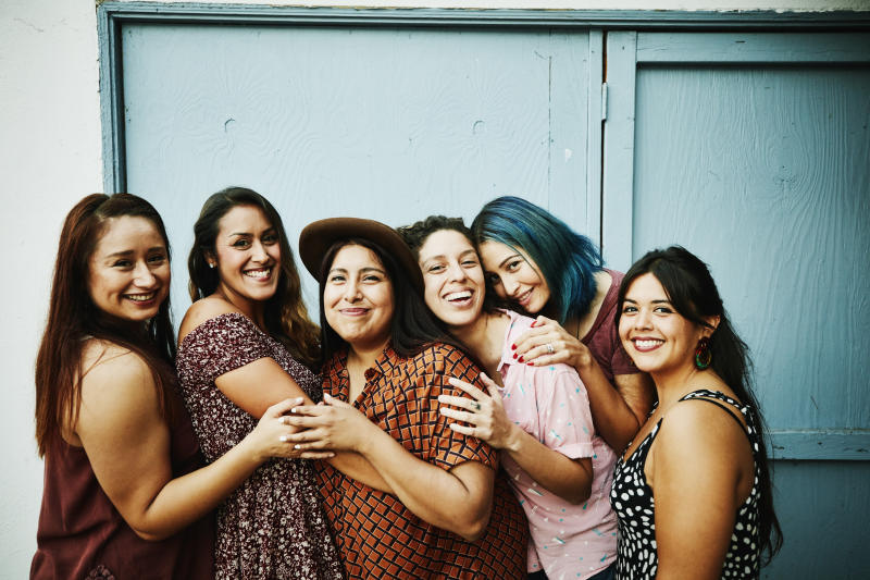 Portrait of female friends embracing in front of blue wall