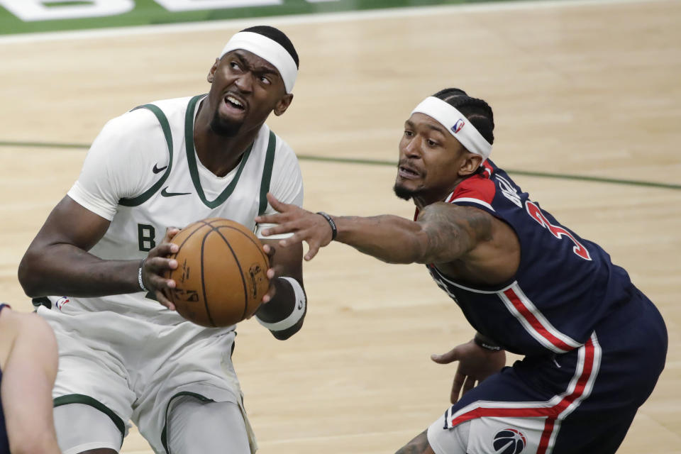 Washington Wizards' Bradley Beal, right, reaches for the ball as Milwaukee Bucks' Bobby Portis drives to the basket during the second half of an NBA basketball game Wednesday, May 5, 2021, in Milwaukee. (AP Photo/Aaron Gash)