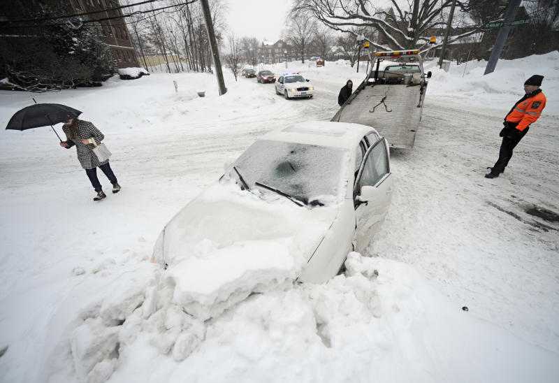 A car that hit a snowbank is towed during a winter storm in Hartford, Conn., Tuesday, Feb. 1, 2011. The storm dumped more snow and a dangerous mix of ice, sleet and rain Tuesday on Connecticut as winter-weary residents worried about roof collapses and how to get to work while utilities braced for power outages. (AP Photo/Jessica Hill)
