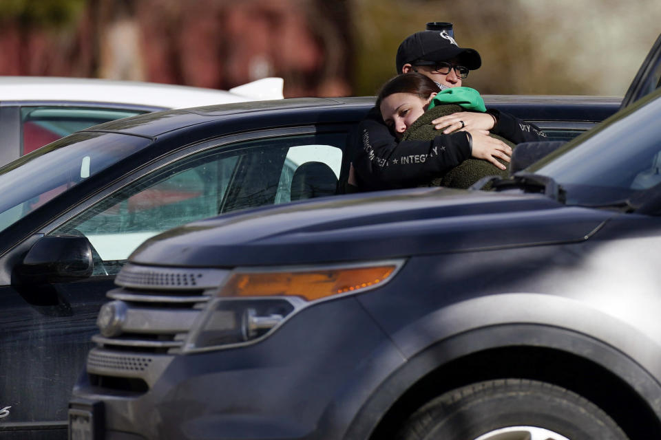 A couple embrace outside the Legacy Assisted Living at Lafayette care facility, Wednesday, Feb. 3, 2021, in Lafayette, Colo. A 95-year-old resident of the assisted care home was taken into police custody Wednesday after allegedly shooting an employee at the center. (AP Photo/David Zalubowski)
