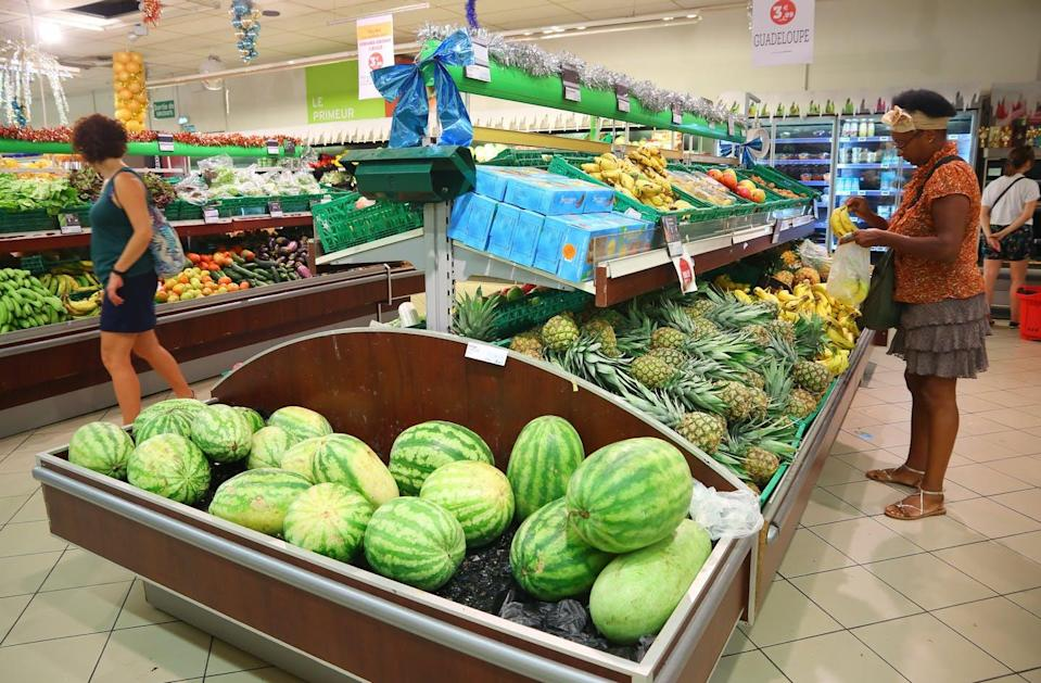 """<span class=""""caption"""">People visit fruit section of a grocery store on Guadeloupe, an island group in the southern Caribbean Sea.</span> <span class=""""attribution""""><span class=""""source"""">(Shutterstock)</span></span>"""
