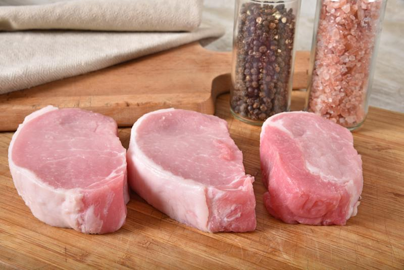Fresh raw pork cutlets on a cutting board