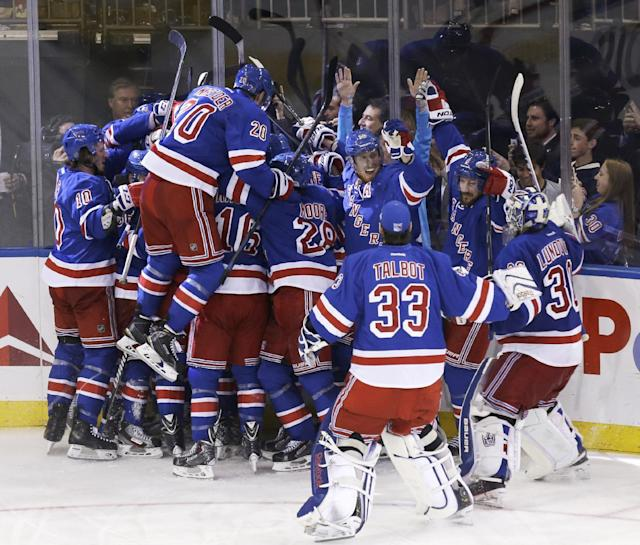 The New York Rangers mob teammate Martin St. Louis after he scored the winning goal during overtime in Game 4 of the NHL hockey Stanley Cup playoffs Eastern Conference finals against the Montreal Canadiens, Sunday, May 25, 2014, in New York. The Rangers defeated the Canadiens in overtime 3-2. (AP Photo/Seth Wenig)