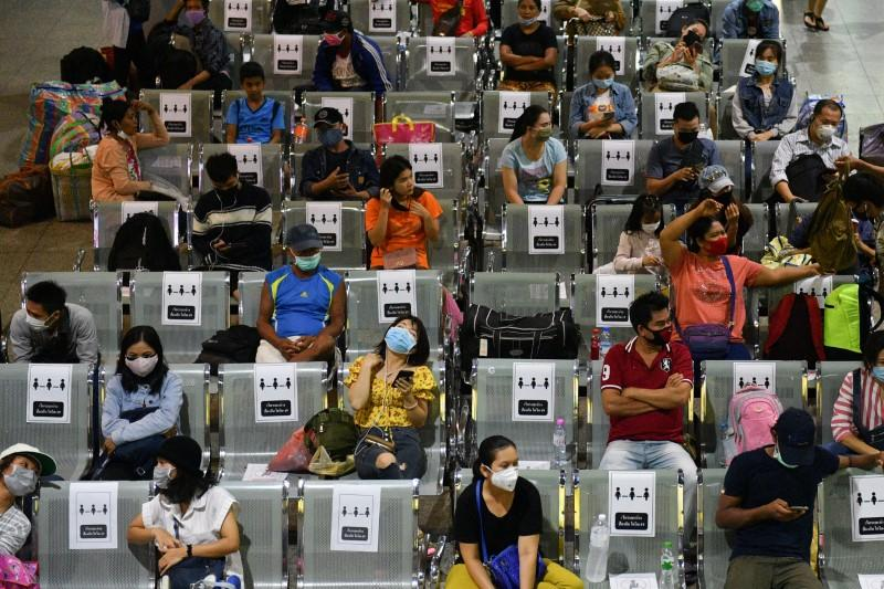 People wearing protective face masks, sit on social distancing benches at a bus station after many workers crowded the terminal station to return to their cities after many activities have been closed due to coronavirus disease (COVID-19) outbreak