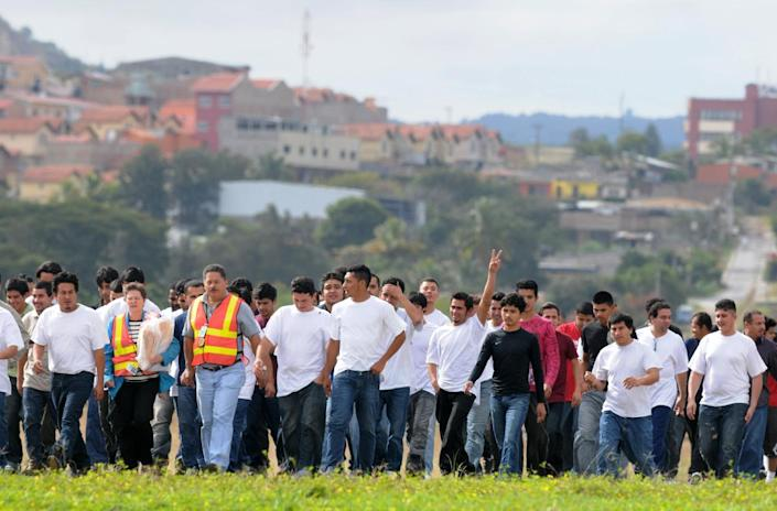 Honduran migrants deported from the United States walk on the tarmac at Toncontin Airport in Tegucigalpa on December 23, 2011 (AFP Photo/Orlando Sierra)