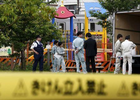 Workers of Tokyo's Toshima ward office and police officers are seen in front of the playground equipment where high levels of radiation were detected at a park in Toshima ward, Tokyo April 24, 2015. REUTERS/Toru Hanai