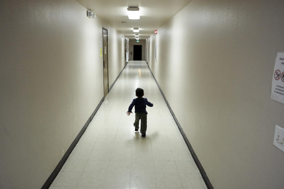 FILE - In this Dec. 11, 2018, file photo, an asylum-seeking boy from Central America runs down a hallway after arriving from an immigration detention center to a shelter in San Diego. A court-appointed committee has yet to find the parents of 628 children separated at the border early in the Trump administration. (AP Photo/Gregory Bull, File)
