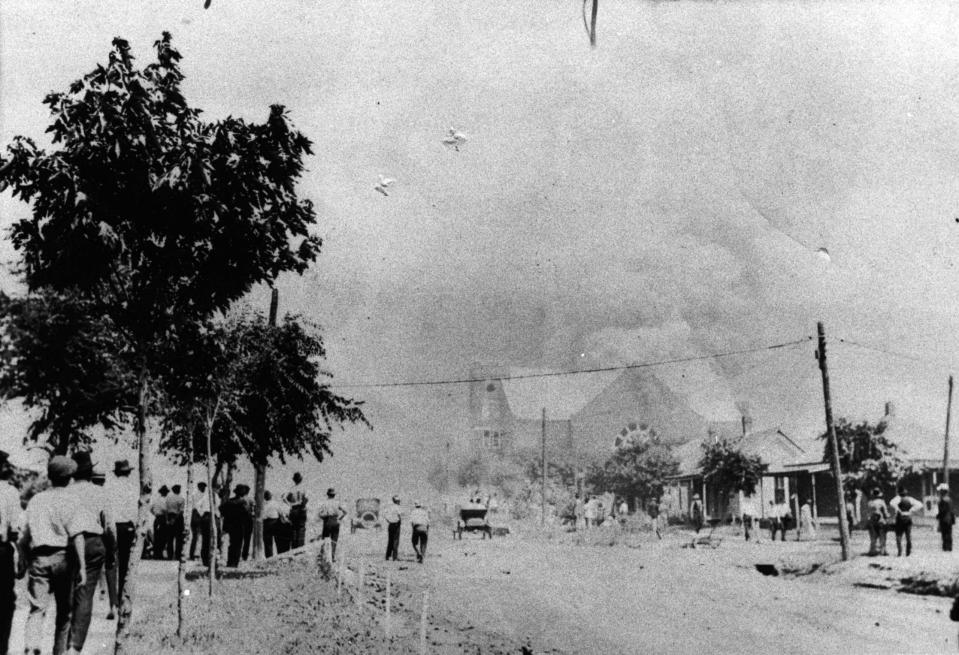 FILE - This photo provided by the Department of Special Collections, McFarlin Library, The University of Tulsa shows a crowd watching the Mt. Zion Baptist Church burn during the June 1, 1921, Tulsa Race Massacre in Tulsa, Okla. (Department of Special Collections, McFarlin Library, The University of Tulsa via AP, File)