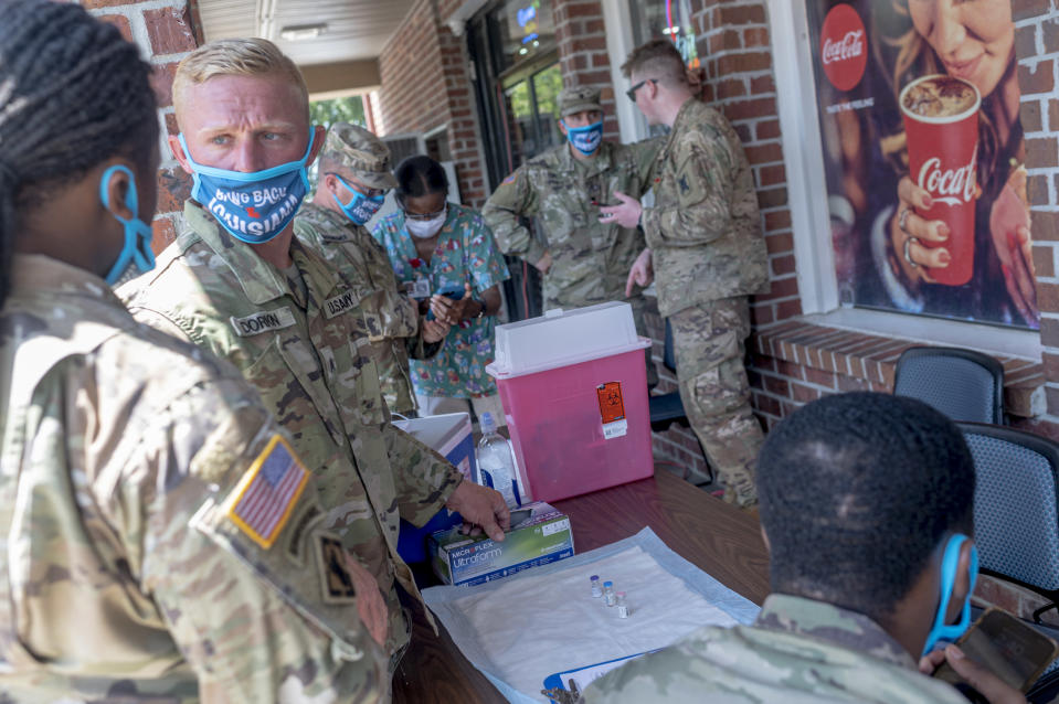 Members of the National Guard prepare vaccine doses outside of a gas station in LaPlace, La., June 17, 2021. (Emily Kask/The New York Times)