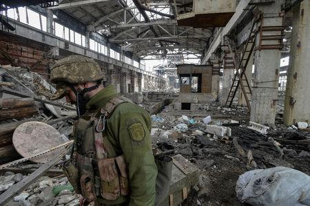 FILE PHOTO: Ukrainian serviceman guards an area on front line at industrial zone of Avdiyivka