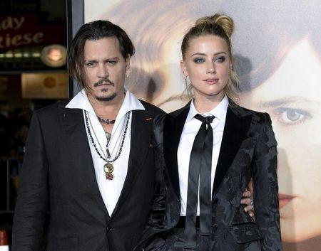 """Cast member Amber Heard and husband Johnny Depp pose during the premiere of the film """"The Danish Girl,"""" in Los Angeles, California November 21, 2015. REUTERS/Kevork Djansezian/File Photo"""