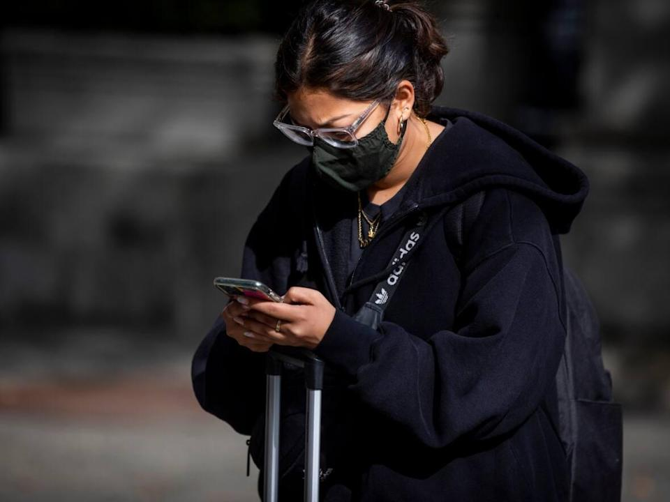 A person looks at their cellphone while wearing a protective face mask in downtown Vancouver, British Columbia on Monday, Oct. 4, 2021.  (Ben Nelms/CBC - image credit)