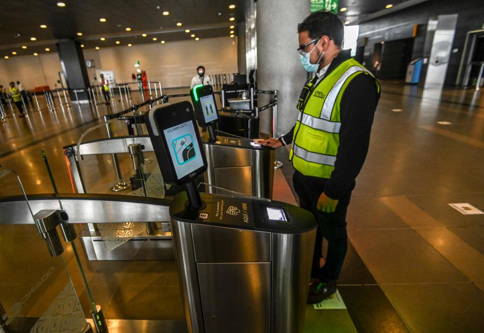 A worker performs a new boarding procedure at El Dorado international airport in Bogota on June 25, 2020 during a press tour to show the biosecurity protocols for an eventual gradual reopening of commercial flights amid the COVID-19 pandemic. (Photo by JUAN BARRETO/AFP via Getty Images)