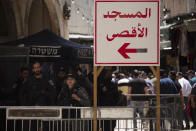 """Israeli police stand at a checkpoint with a sign in Arabic that reads, """"Al-Aqsa Mosque,"""" in the Old City of Jerusalem for Friday prayers during the Muslim holy month of Ramadan, on Friday, April 23, 2021. Israeli police say 44 people were arrested and 20 officers were wounded in a night of chaos in Jerusalem, where security forces separately clashed with Palestinians angry about Ramadan restrictions and Jewish extremists who held an anti-Arab march nearby. (AP Photo/Maya Alleruzzo)"""