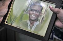 A man holds a portrait of Rezaul Karim Siddique, an English literature professor and prominent secular activist who was killed near his home in Rajshahi city in April 2016 (AFP Photo/MD. ABDULLAH IQBAL)
