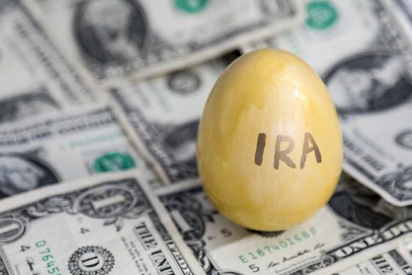 """Colored egg labeled """"IRA,"""" on a floor of dollar bills"""