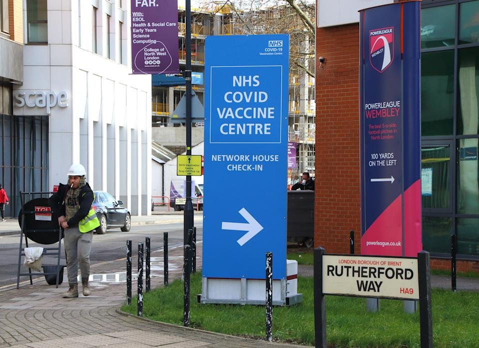Signage directs the public to the NHS vaccination centre. A steady stream of elderly people with pre-booked appointments at the new Covid-19 Vaccination hub at the�Olympic Office Centre, near London's Wembley Stadium. It is one of 10 new large scale Vaccination centres opened this week, to join the seven already in use across the country. So far 4.9 million people across the UK have received the first dose of vaccine and the government aims for that number to rise to 15 million by 15 February. (Photo by Keith Mayhew / SOPA Images/Sipa USA)