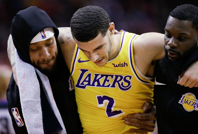 Los Angeles Lakers guard Lonzo Ball, center, is carried off the court by Michael Beasley, left, and Lance Stephenson after Ball sustained an injury during the second half of the team's NBA basketball game against the Houston Rockets, Saturday, Jan. 19, 2019, in Houston. (AP Photo/Eric Christian Smith)