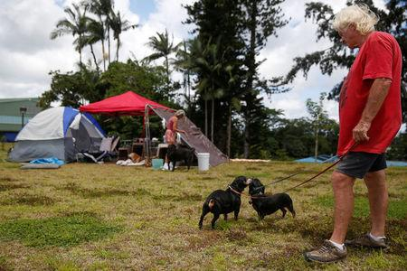 Eddie McLaren, of Kapoho, walks two of his five dogs near his tents at a Red Cross evacuation center in Pahoa during ongoing eruptions of the Kilauea Volcano in Hawaii, U.S., May 15, 2018.  REUTERS/Terray Sylvester