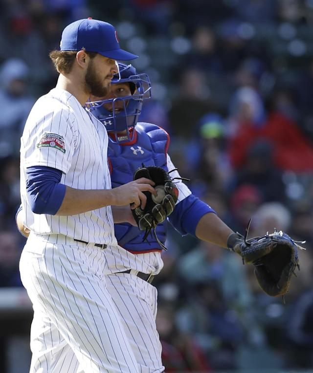 Chicago Cubs catcher Welington Castillo, rear, talks with relief pitcher Justin Grimm during the eighth inning of a baseball game against the Cincinnati Reds in Chicago, Friday, April 18, 2014. (AP Photo/Nam Y. Huh)