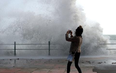 A woman take a photograph as waves crash up onto Penzance seafront - Credit: Matt Cardy/Getty