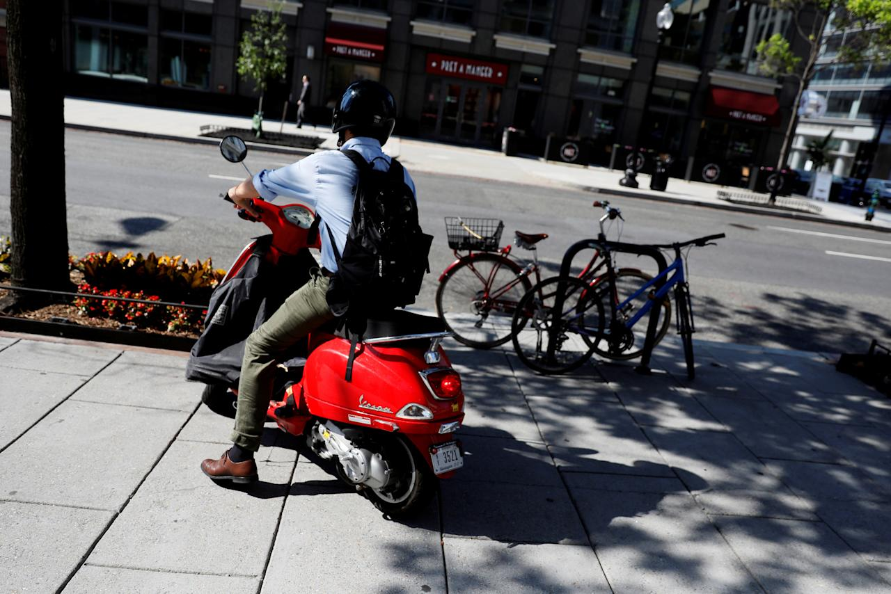 FILE PHOTO: A commuter parks his Vespa scooter on a sidewalk in Washington, U.S. June 12, 2017.  REUTERS/Jonathan Ernst/File Photo